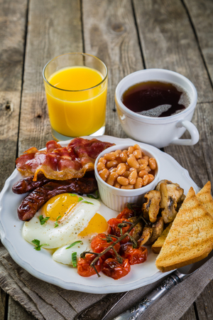 Full english breakfast - eggs, bacon, beans, toast, coffee and juice Stock Photo