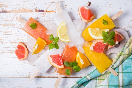 Colorful popsicles on rustic wood background, copy space