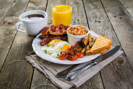 Full english breakfast - eggs, bacon, beans, toast, coffee and juice, rustic wood background 版權商用圖片 - 80120815