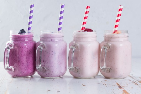 Selection of colorful detox berry drinks on wood background