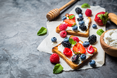 Selection of toasts with cheese peanut butter and berries, rustic background Stock Photo - 82187876