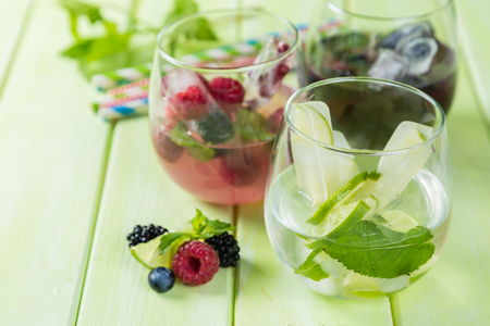 Selection of colorful infused waters in glasses, rustic background