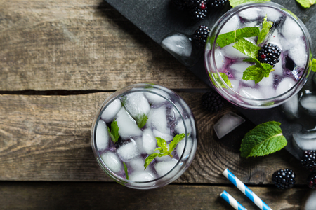 Blackberry mojito and ingredients on rustic background