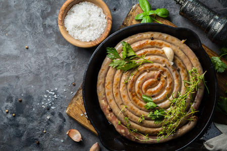 Barbeque sausages on cast iron pan with herbs, copy space Stok Fotoğraf