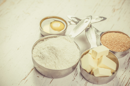 Baking ingredients in measuring cups, white wood background