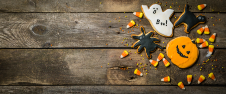 Halloween concept with cookies and candies, rustic wood background