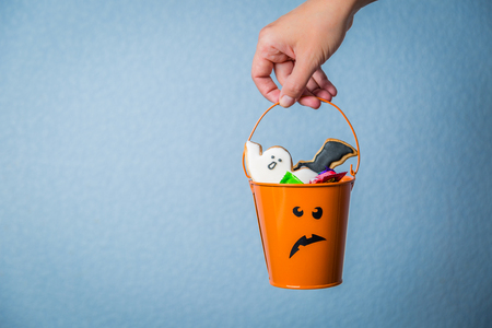 celebrate: Halloween concept - hand holding basket with candies