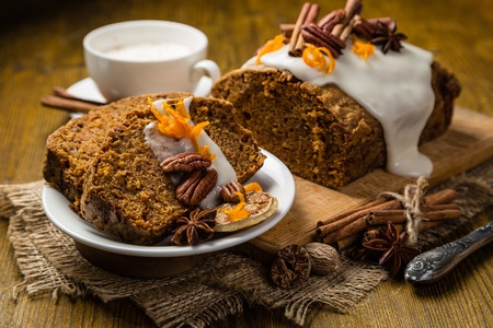 Carrot cake with autumn decorations, rustic wood background