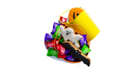 Halloween concept - basket with candies and ccokies, isolated on white