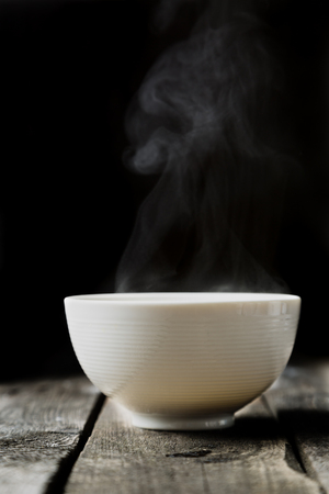 Steaming bowl on rustic wood background