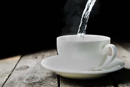 Pouring water in cup Stock Photo