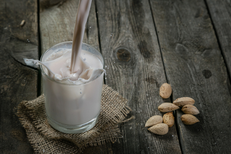Pouring almon milk on rustic wood background