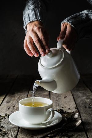 흰색 컵에 차를 붓는 다.