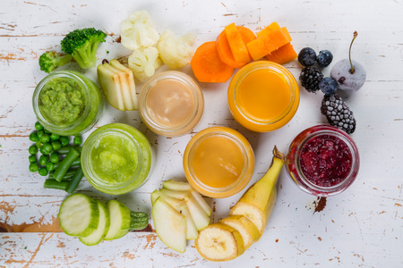 Colorful baby food purees in glass jars Banco de Imagens