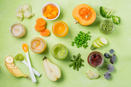 Colorful baby food purees in glass jars Фото со стока