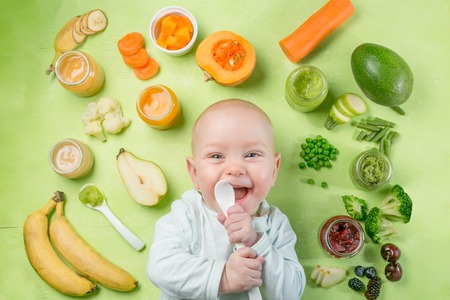 Colorful baby food purees in glass jars Imagens