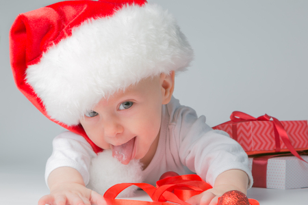 Baby lying with presents in santa hat on grey background