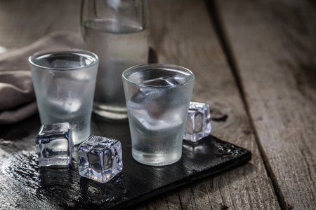 Vodka in shot glasses on rustic wood background Imagens - 91596770