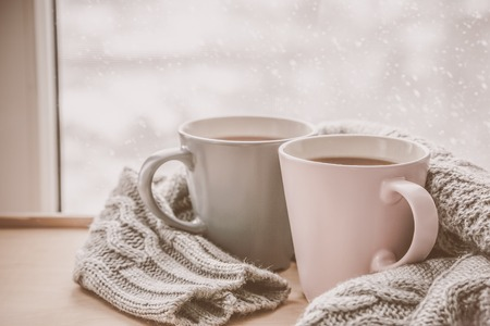 Valentine's day concept - two cups of tea in front of snow background, toned Stok Fotoğraf