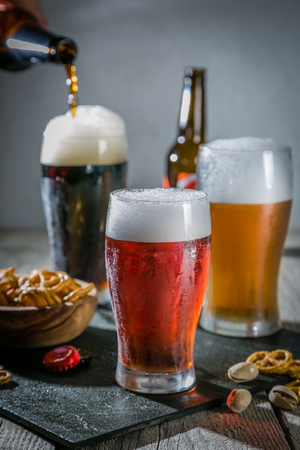 Different types of beer on rustic wood background