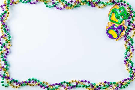 Mardi gras carnival background - beads and mask on white background, isolated