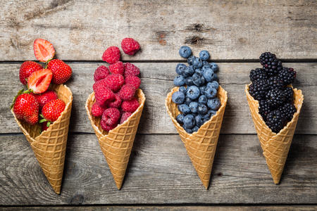Selection of summer berries in ice cream cones on rustic background. Healthy dessert, lifestyle.