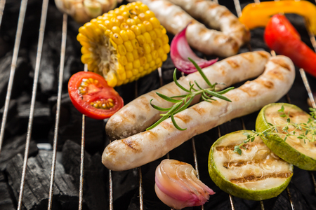 Preparing grilled sausage and vegetables Stock Photo