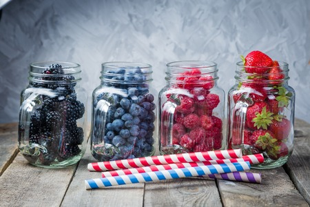 Berries in glass jars - homemade jam, smoothie, low fat dessert