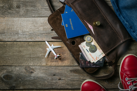 Traveling concept - essentials, camera, phone and plane model on wooden background