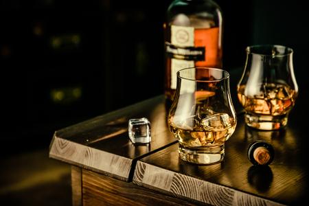 素朴な背景に氷を持つメガネのウイスキー