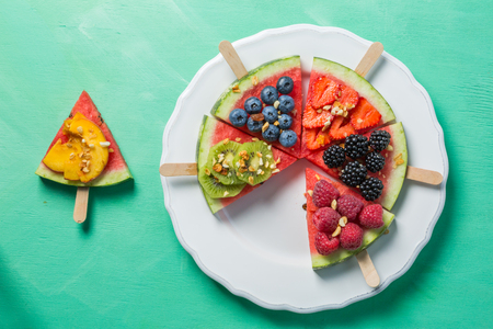Watermelon pizza - slices with berries and fruits, granola. Fresh low carb diet