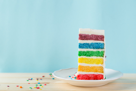 Birthday background - striped rainbow cake with white frosting 写真素材 - 96244509