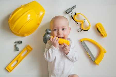 Baby playing with construction tools on white background