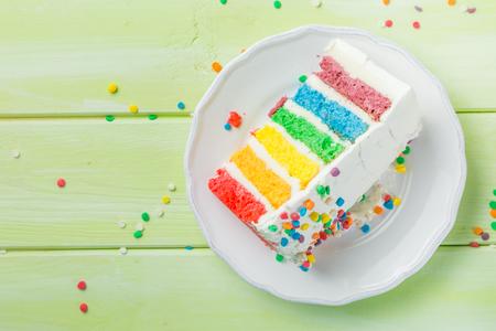 誕生日の背景 - 白いフロスティングとストライプレインボーケーキ