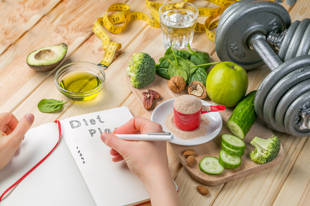 Diet plan concept - selection of green food and note pad Stock Photo