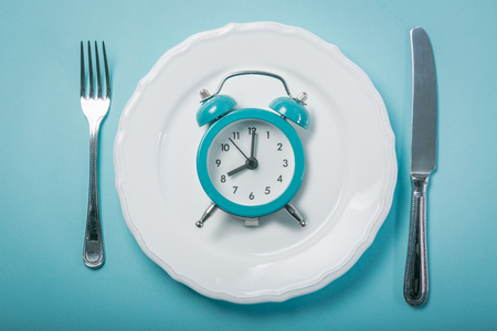 Intermittent fastin concept - empty plate on blue background Imagens - 97349069