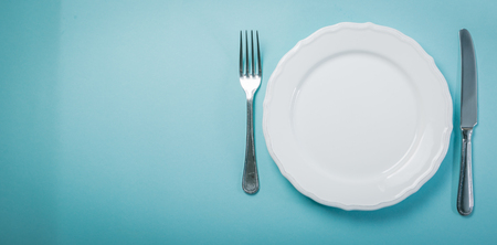 Intermittent fastin concept - empty plate on blue background