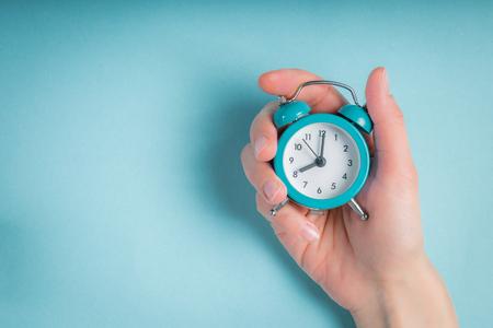 Female hand holding clock