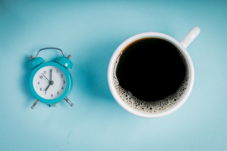 Morning concept - coffee and alarm clock on blue background