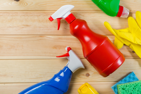 Cleaning concept - cleaning supplies on wood background Stock Photo