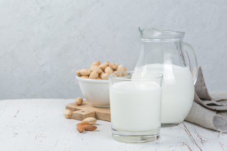Almond milk in glass and jar on wood background