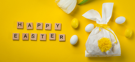 Easter concept - bunny shaped bag with eggs and flowers on bright yellow background, Stock Photo