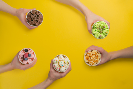 Hands holding cups with different rolled ice cream on bright yellow background Foto de archivo