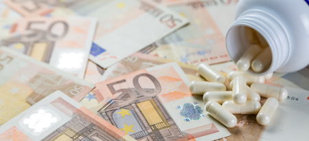 Overpriced drugs concept - pills from container on monet bills