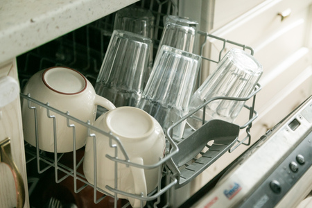 Dishwasher full with clean dishes in kitchen background