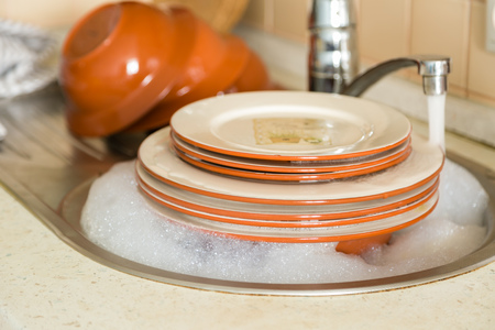 Dishes in the sink with kitchen background Stock Photo