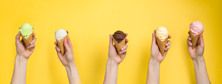 Hands holding ice cream in cones