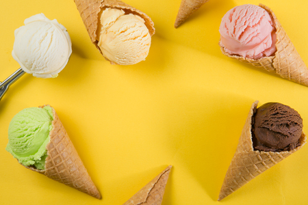 Selection of colorful ice cream scoops on yellow background