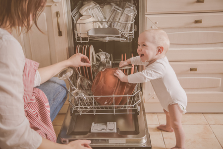 Baby gils helps mother to empty a dishwasher
