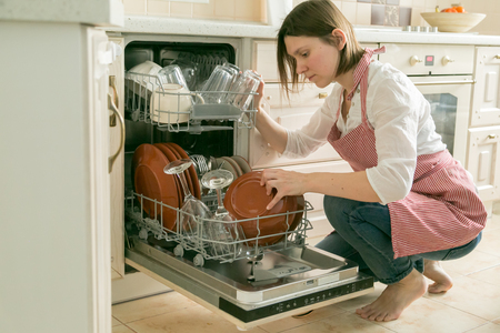 Female takes the dishes from dishwasher. Housework concept